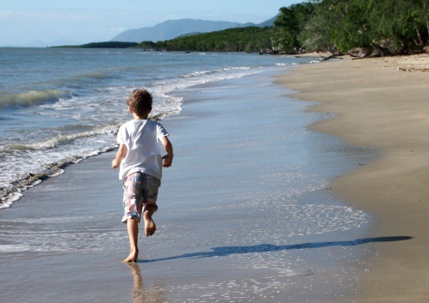 Child running on 4 Mile Beach Queensland Australia