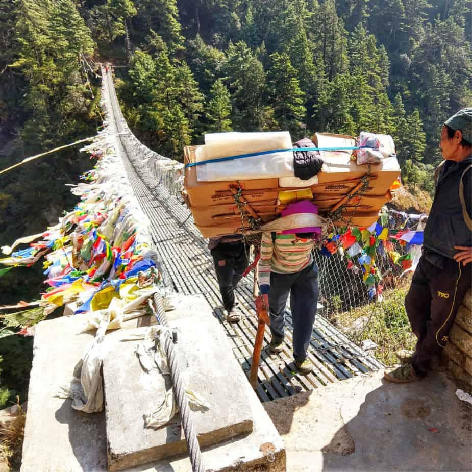 "珠穆朗玛峰大本营徒步穿越桥上的波特"" class ="" wp-image-36529"" srcset ="" https://worldtravelfamily.com/wp-content/uploads/2018/10/Porter-on-the-Everest-Base- Camp-Trek-crossing-bridge.jpg 925w,https://worldtravelfamily.com/wp-content/uploads/2018/10/Porter-on-the-Everest-Base-Camp-Trek-crossing-bridge-150x150.jpg 150w,https://worldtravelfamily.com/wp-content/uploads/2018/10/Porter-on-the-Everest-Base-Camp-Trek-crossing-bridge-300x300.jpg 300w,https://worldtravelfamily.com /wp-content/uploads/2018/10/Porter-on-the-Everest-Base-Camp-Trek-crossing-bridge-768x768.jpg 768w,https://worldtravelfamily.com/wp-content/uploads/2018/ 10 /珠穆朗玛峰基地营穿越徒步桥100x100.jpg 100w"" size =""(max-width:925px)100vw,925px"