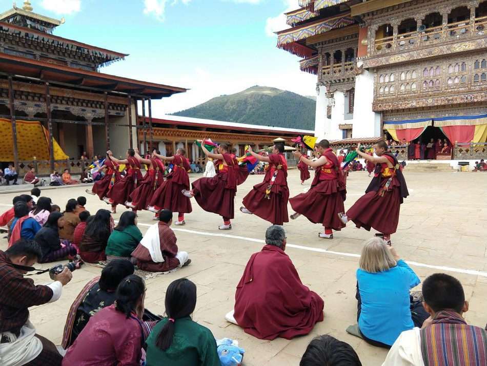 Tourists and locals watching a festival in Bhutan