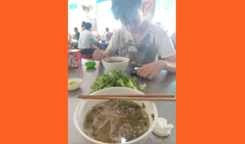 Eating Bun Bo Hue at a noodle shop in Hue City