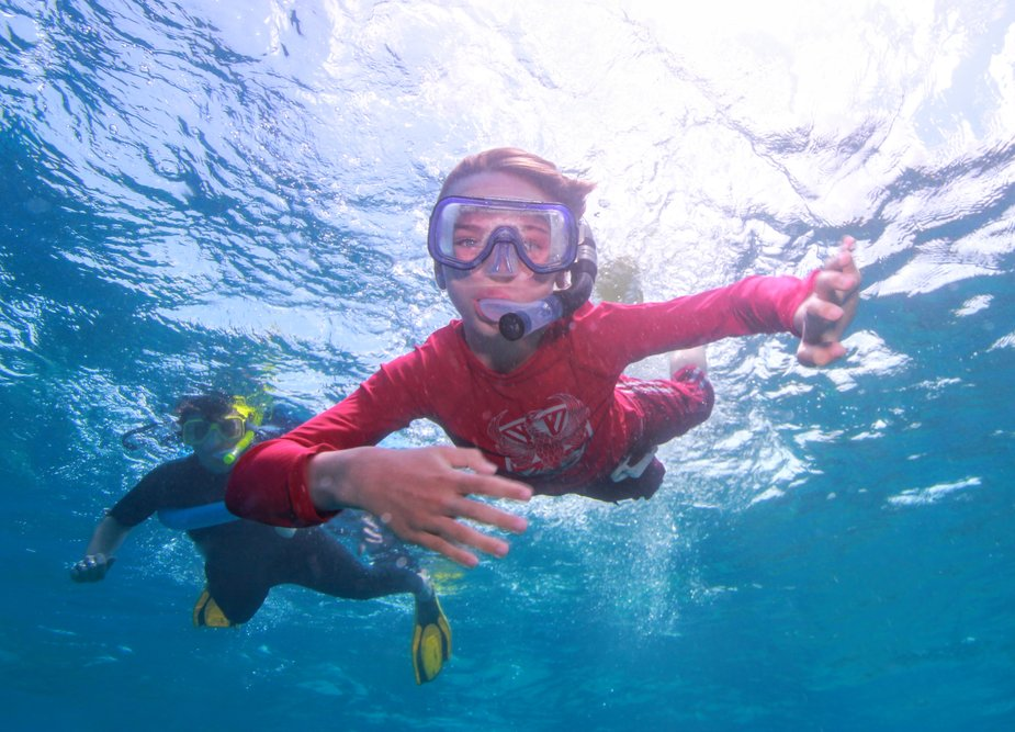 Child snorkelling on the great barrier reef from Port Douglas