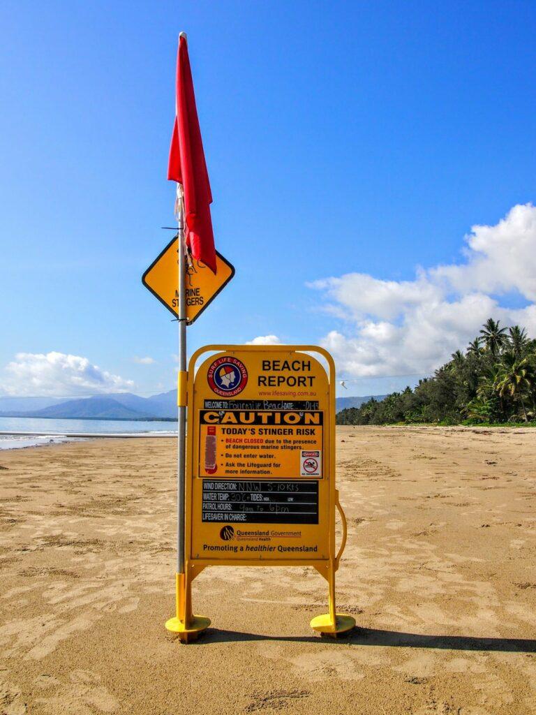 Port Douglas Beach Closed Sign on sandy beach