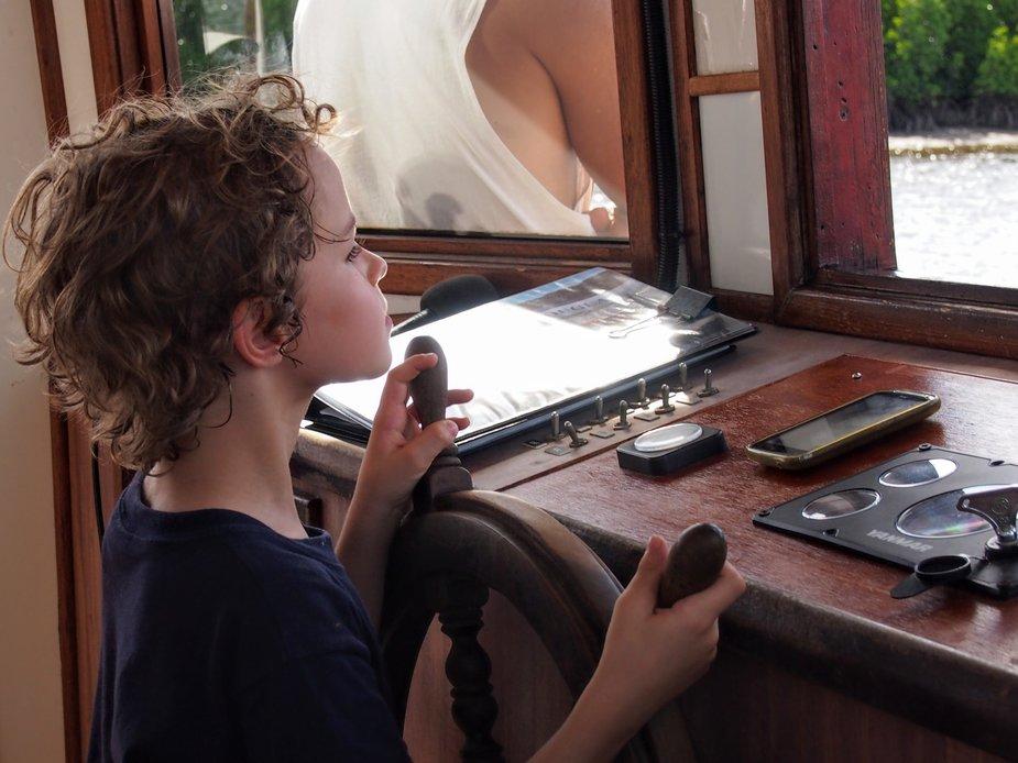 Child driving The Lady Douglas River Cruise Boat in Port Douglas Australia