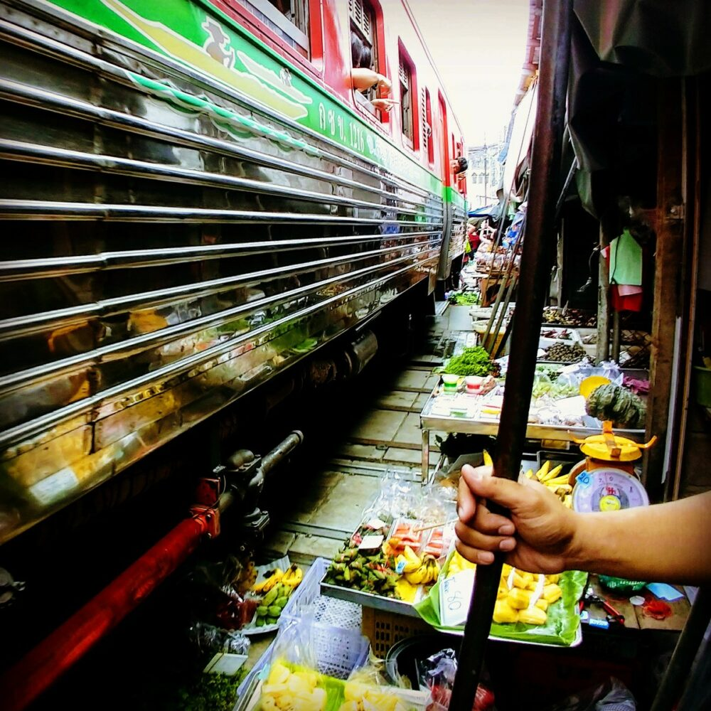 Train going through a market in Thailand. Thailand as a travel destination for families
